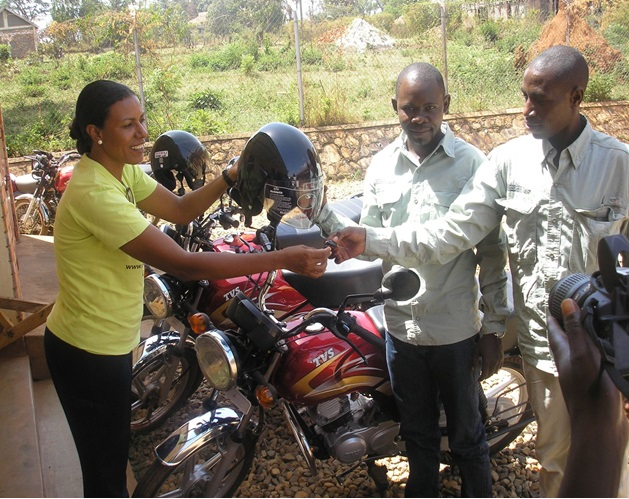 Lilly handing over to Bosco and Livas of Kiziranfumbi Sub County